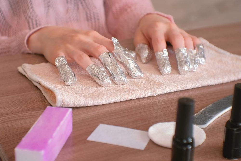 ネイルオフでアルミパックをする女性の手元