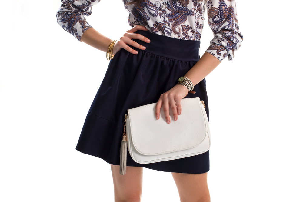 白い革ハンドバッグを持った女性