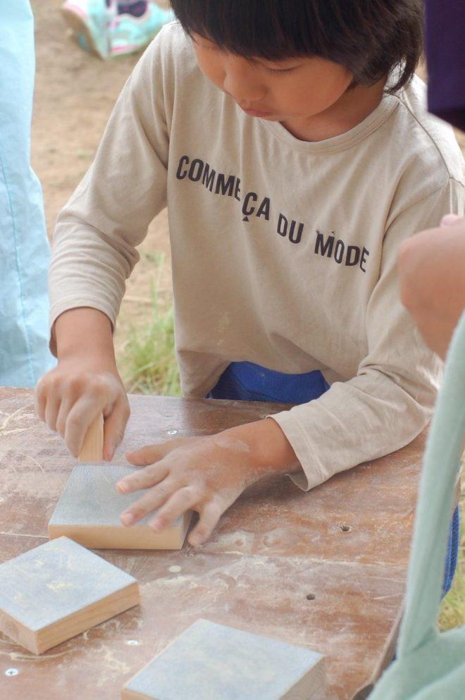 写真は、鴨川で開催される「あわアースひろば」より、木工屋さんの木を磨くお仕事。通帳型のあわっこマネーでは、子どもがお仕事をして貯めたお金で、買い物ができます。