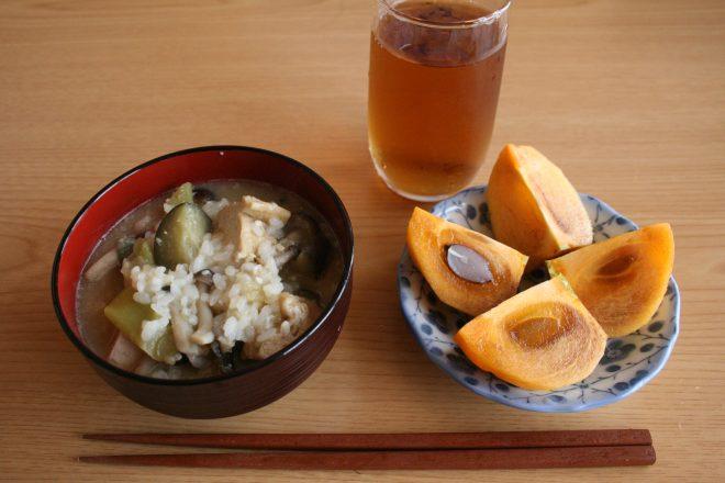 夕飯の残りで作った雑炊と、稲刈りの最中にもいでもらった柿の朝ごはん