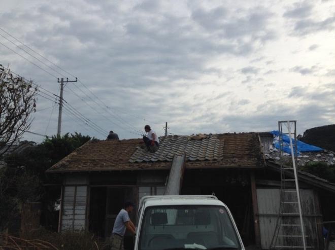 台風により損傷した納屋の屋根。皆で力を合わせて瓦を下ろす